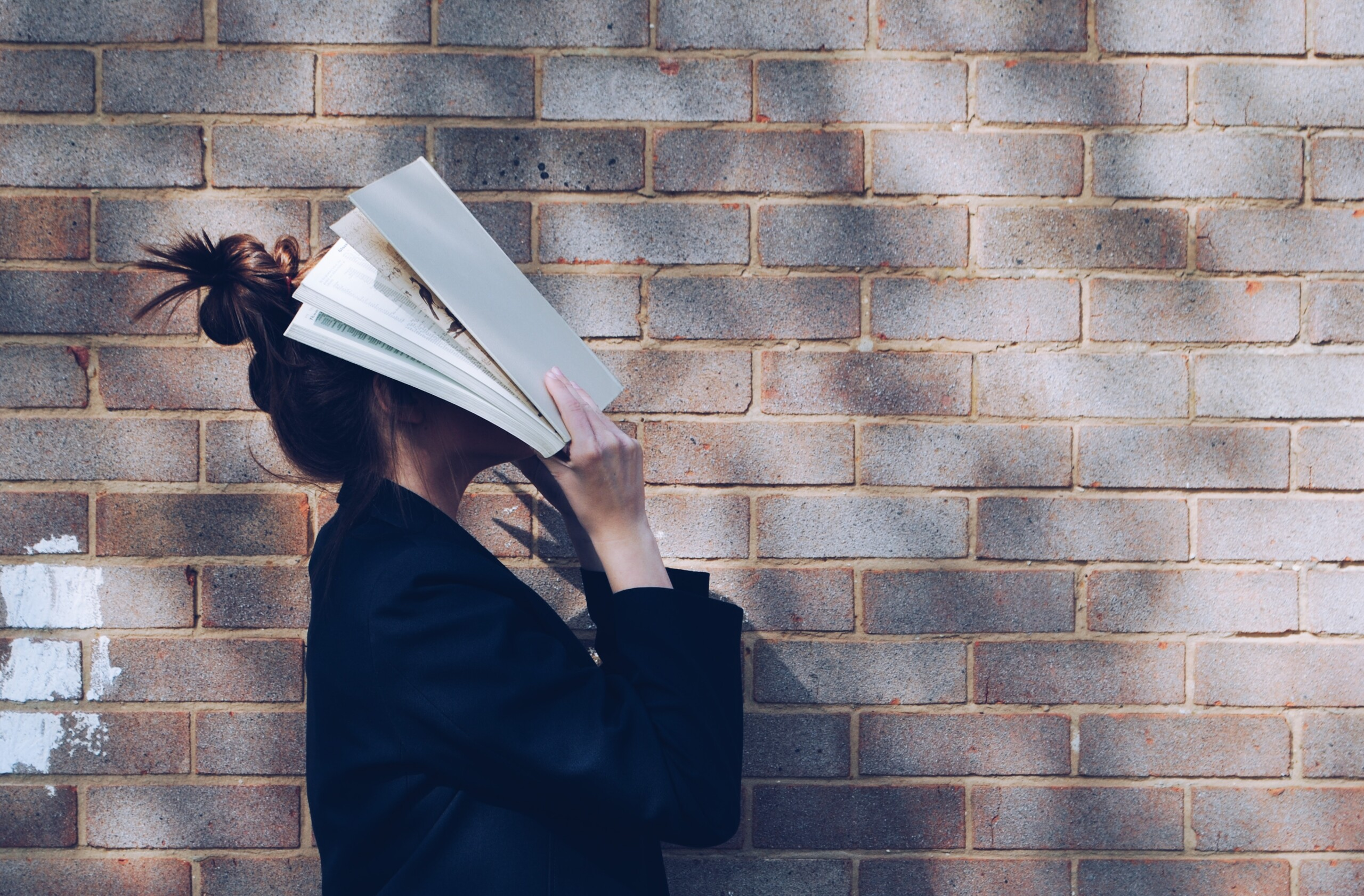 woman covering her face with white book